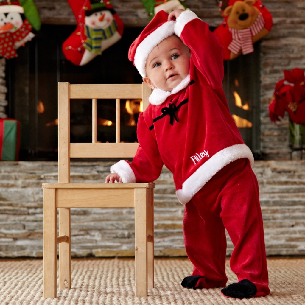 Baby in a personalized Santa costume leaning on a chair in front of the fireplace with stockings hanging in the background_by_Personal Creations