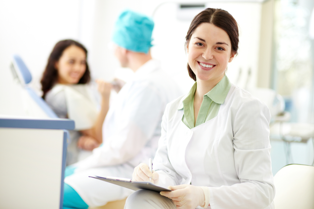 Pretty nurse looking at camera with smile on background of dentist and patient